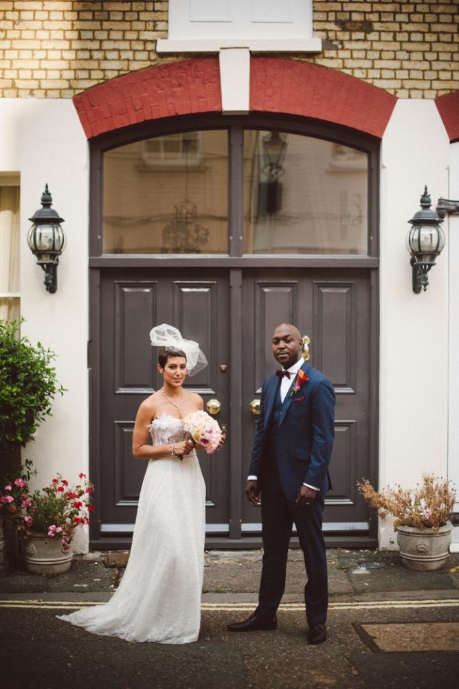 Man & Wife looking at camera infront of door