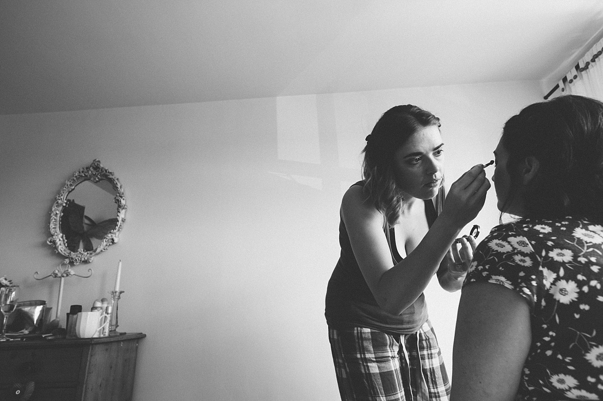 bridesmaid putting wedding makeup on Bride at alternative wedding