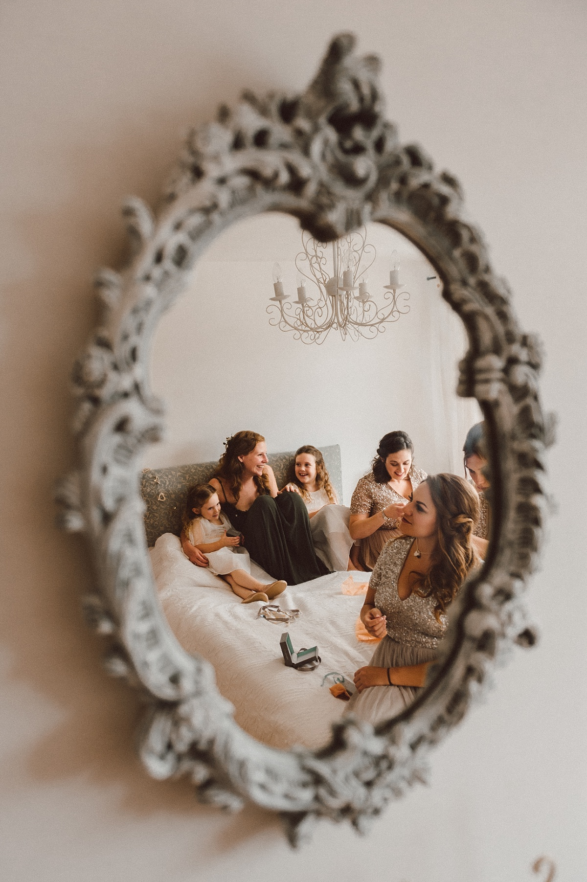 picture on mirror of bridesmaids on bed