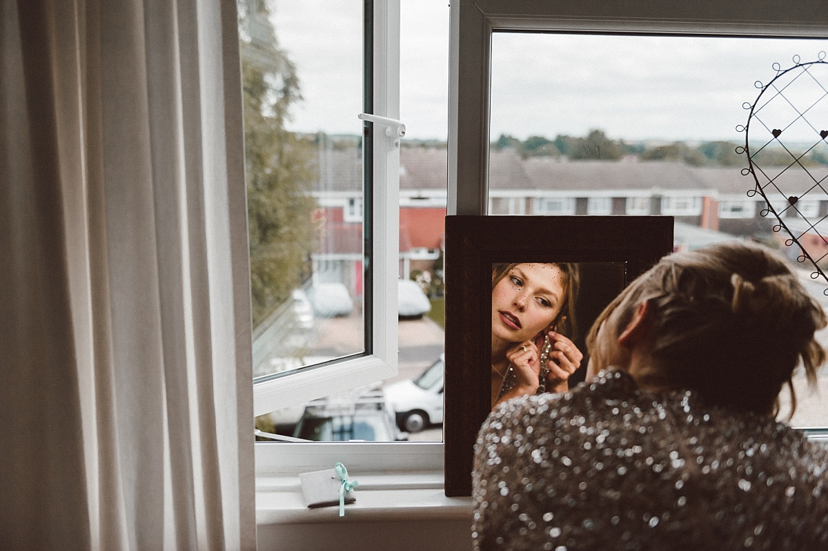 bridesmaid looking into mirror putting on earrings