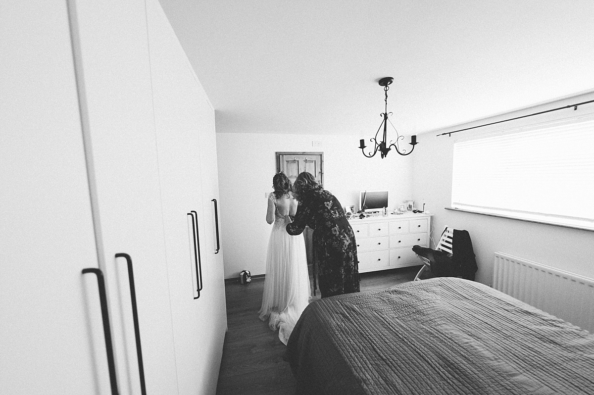 photo of mum helping daughter into wedding dress