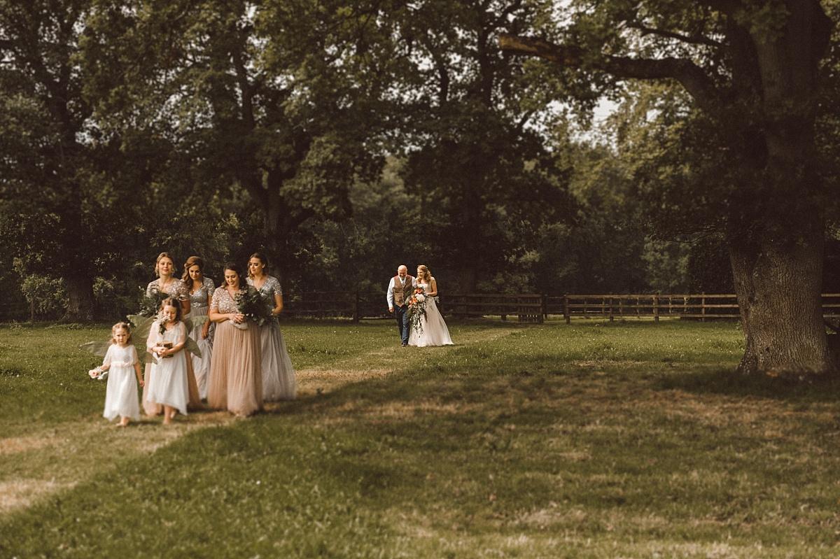wedding party walking across field followed by Bride