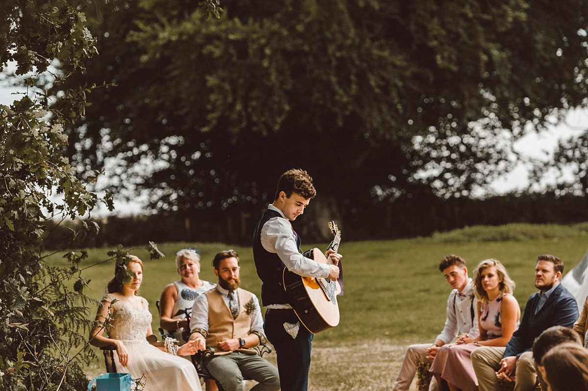 Guest playing guitar at outdoor wedding