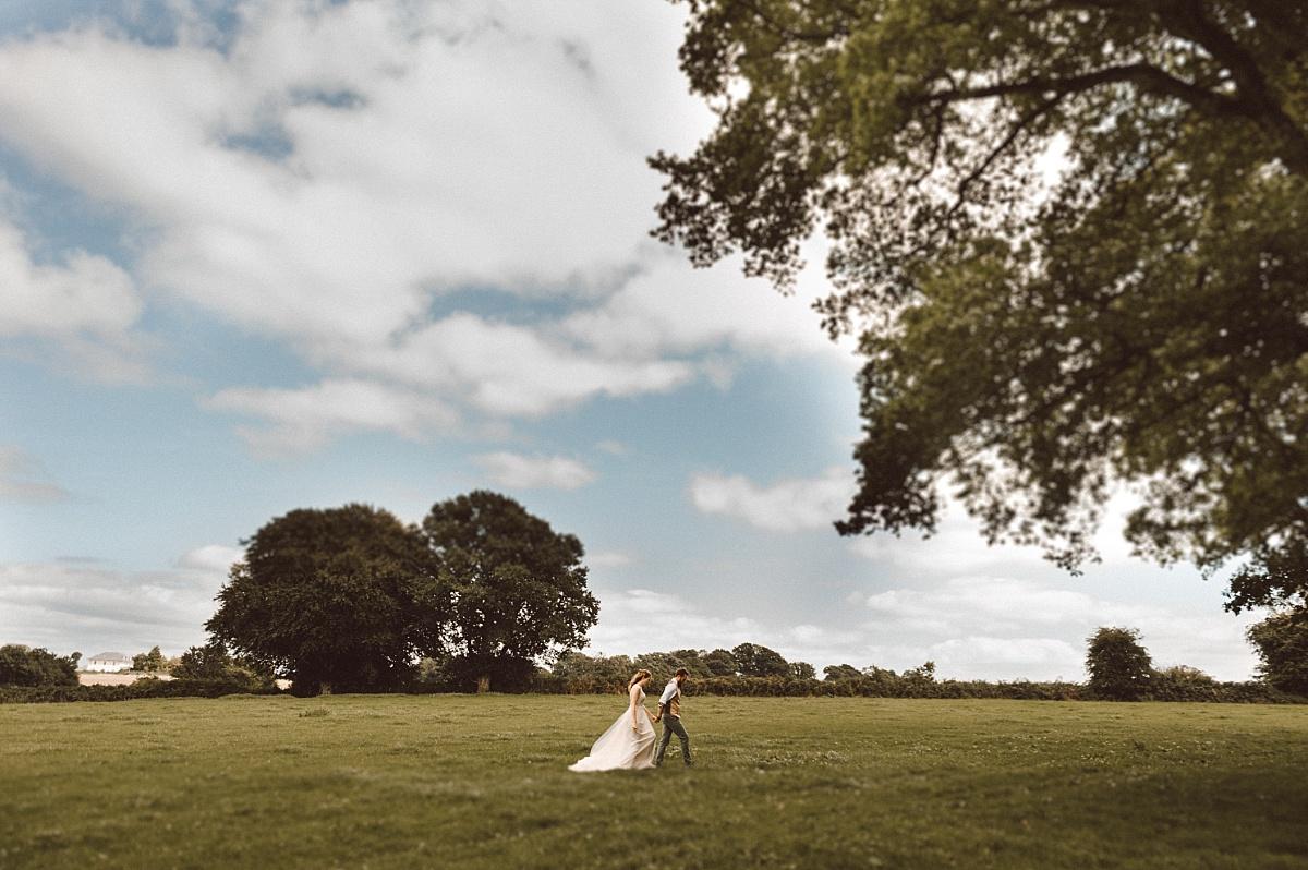 Photo of Bride and Groom walking across open field