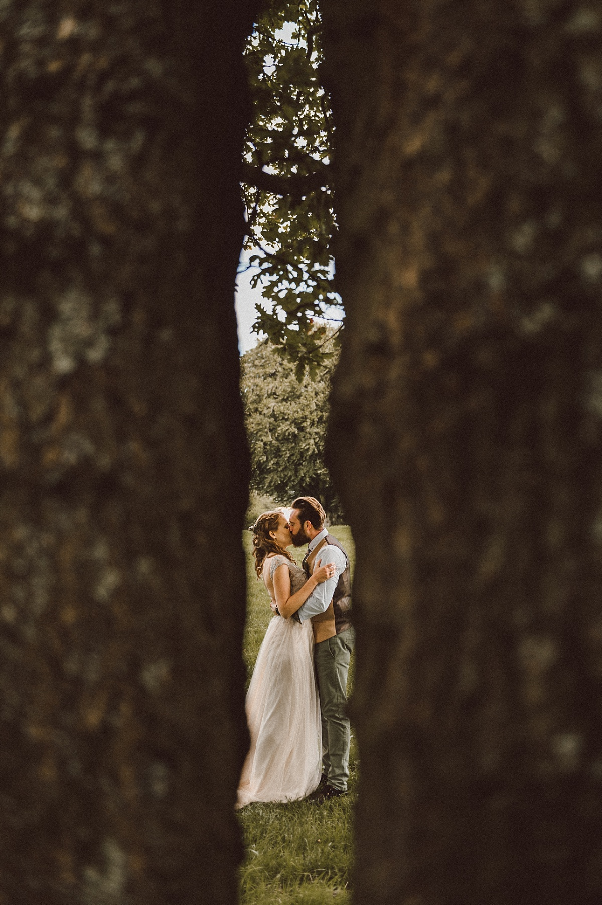 Photo looking through trees at couple kissing