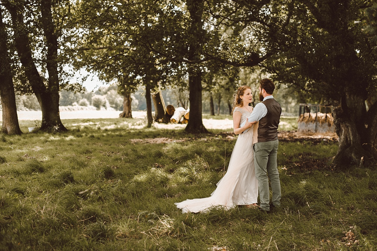 Cool Bride and cool Groom standing in field hugging each other
