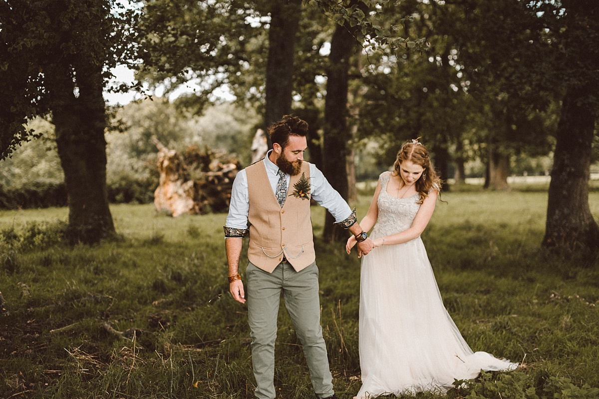 Groom holding brides hand in green field