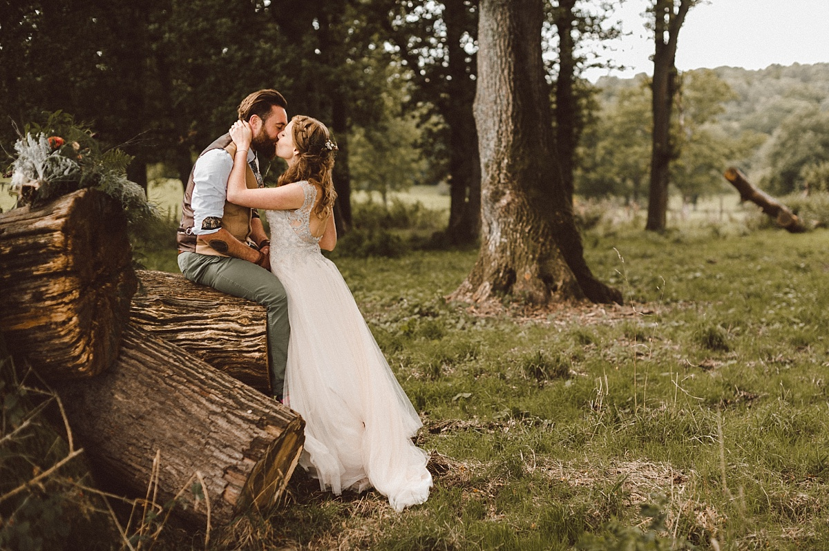 Groom sitting on rustic logs while kissing his Bride
