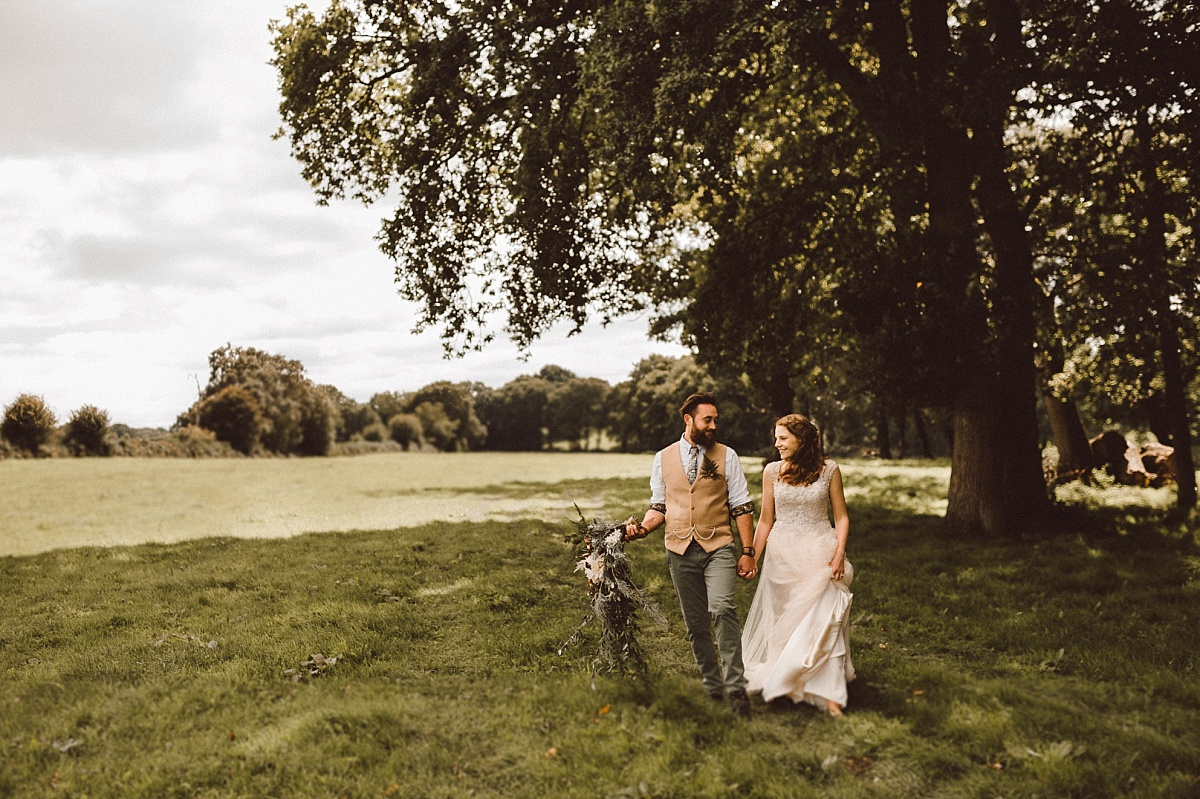 Hipster couple walking through field atalternative wedding
