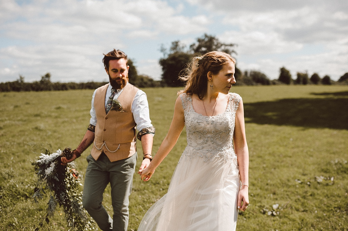 bride and groom holding hands in Green field