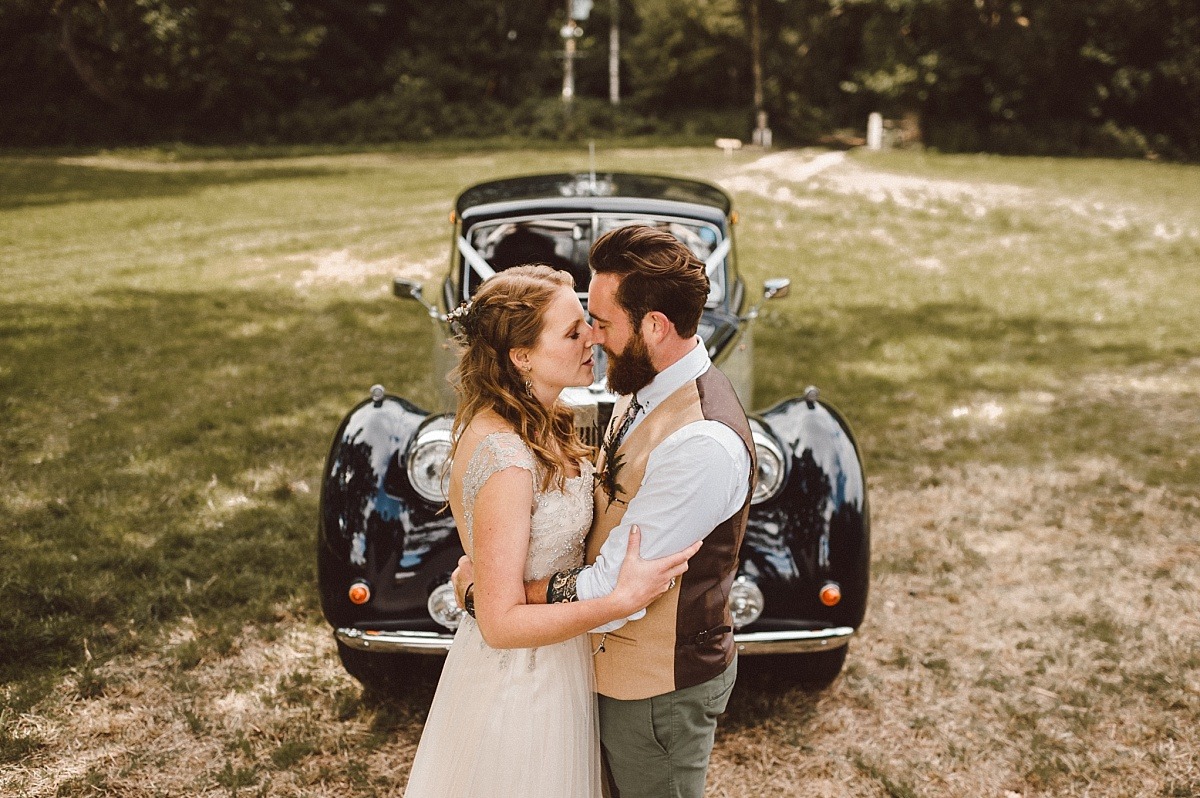 Boho couple infront of classic wedding car