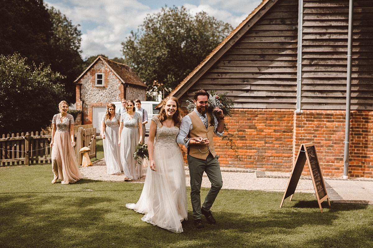 Boho couple arring at village hall on their wedding day