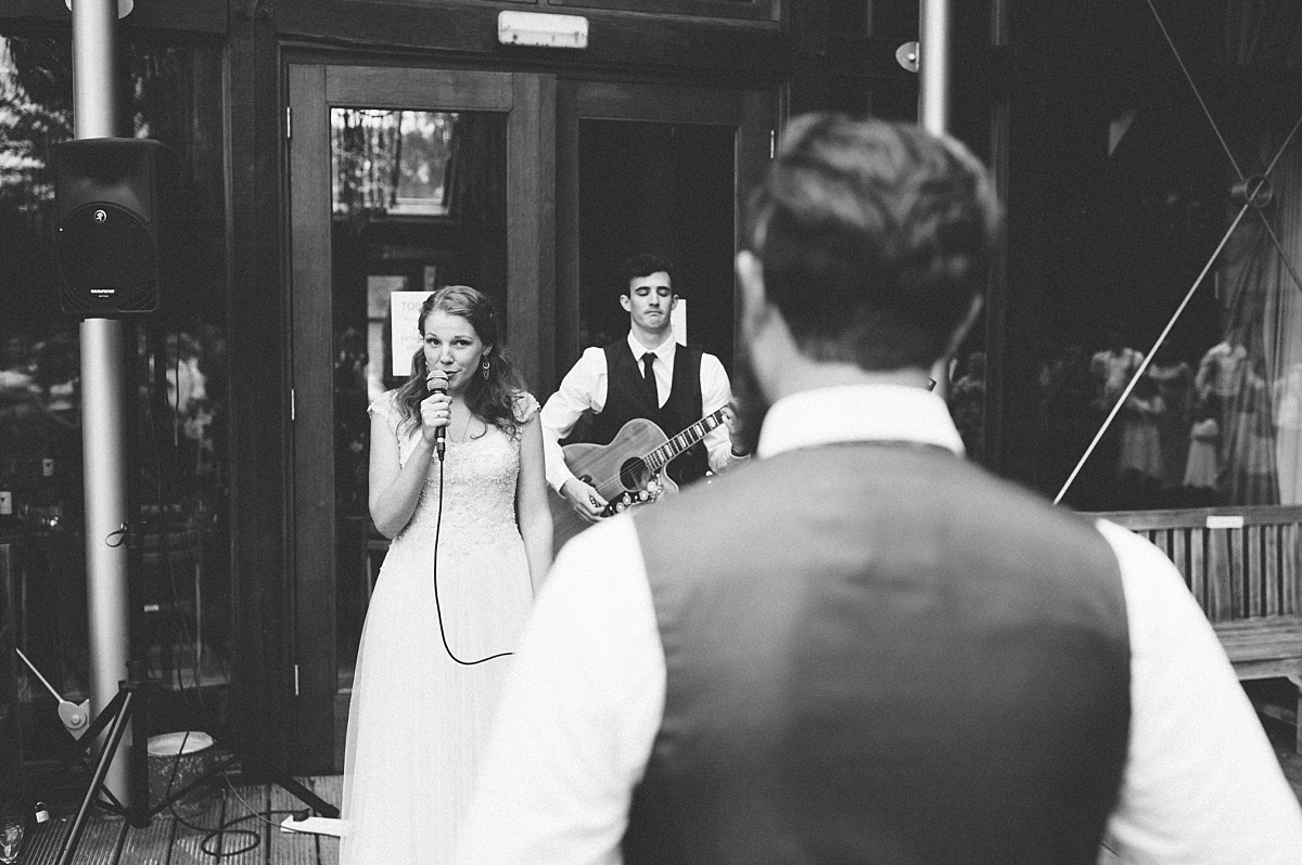black & white photo of bride singing song for Groom