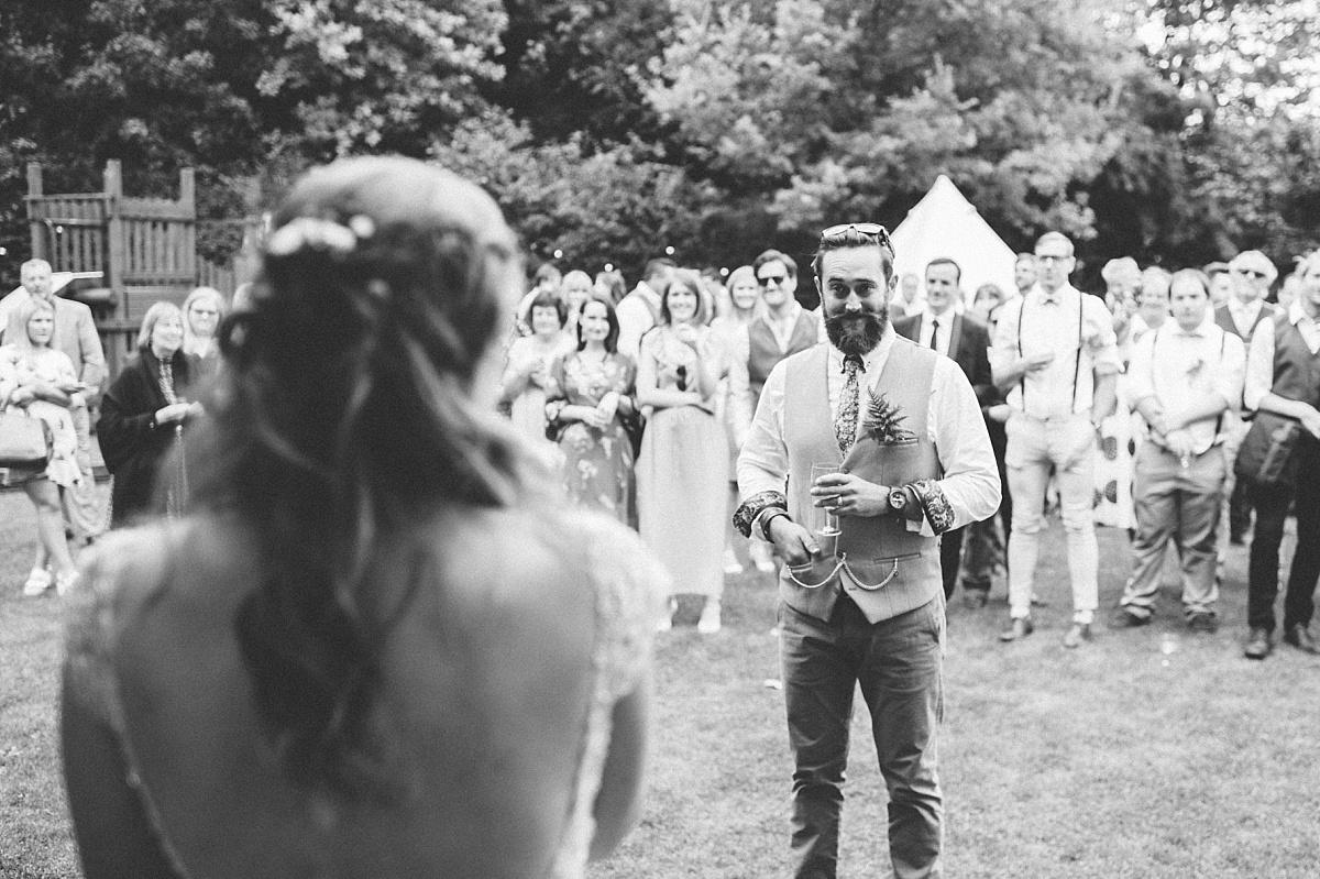 Black & white photo of Groom watching bride singing