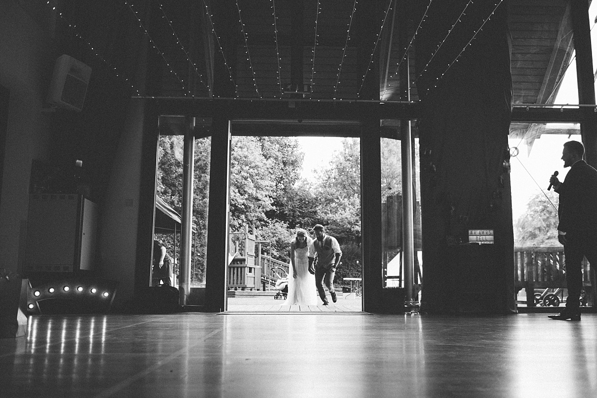 Black & white photo of couple entering wedding meal room