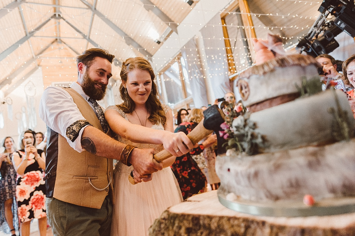 Couple cutting wedding cake in village hall