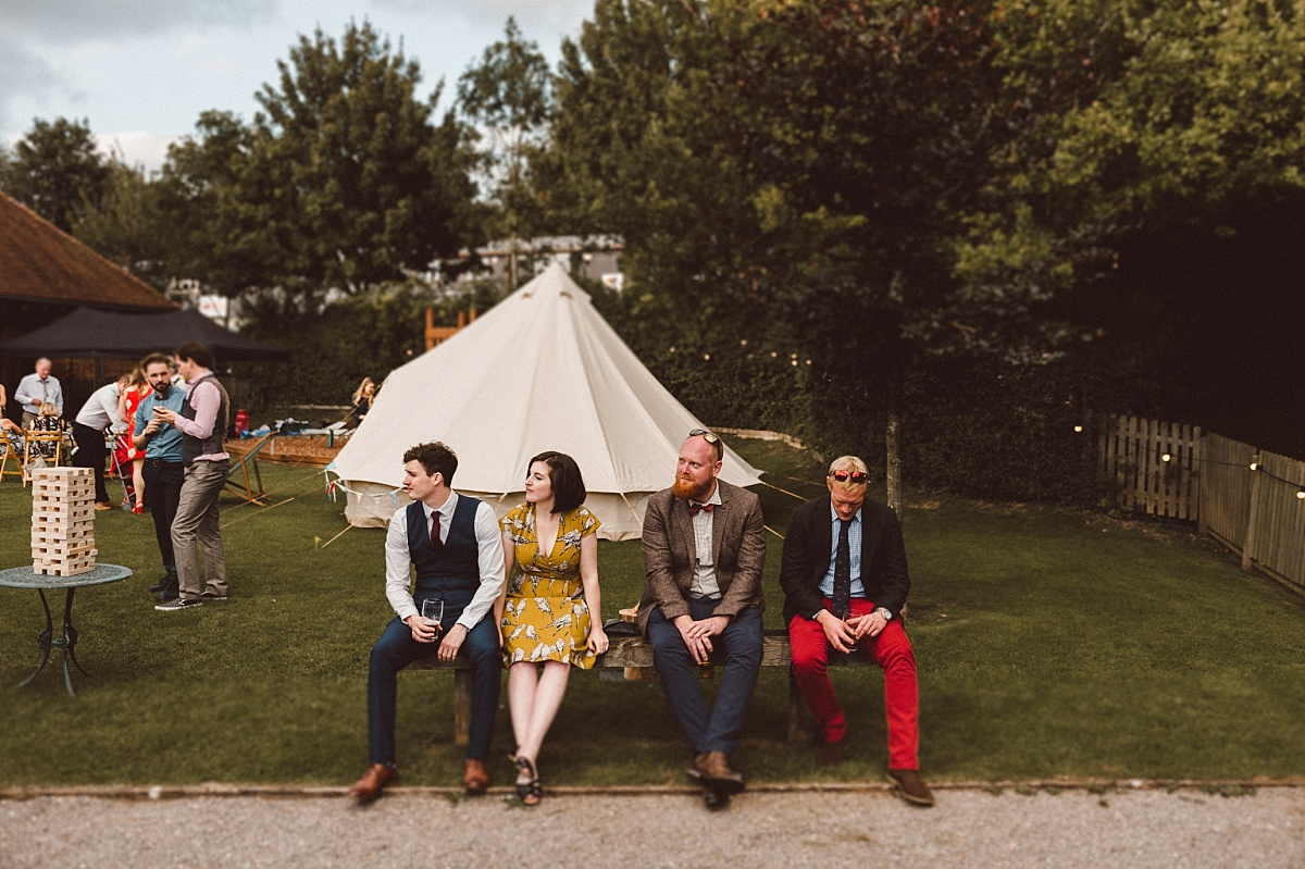 Hipster wedding guests sitting in bench
