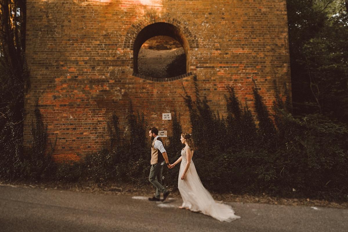 Hipster wedding couple walking under brick bridge