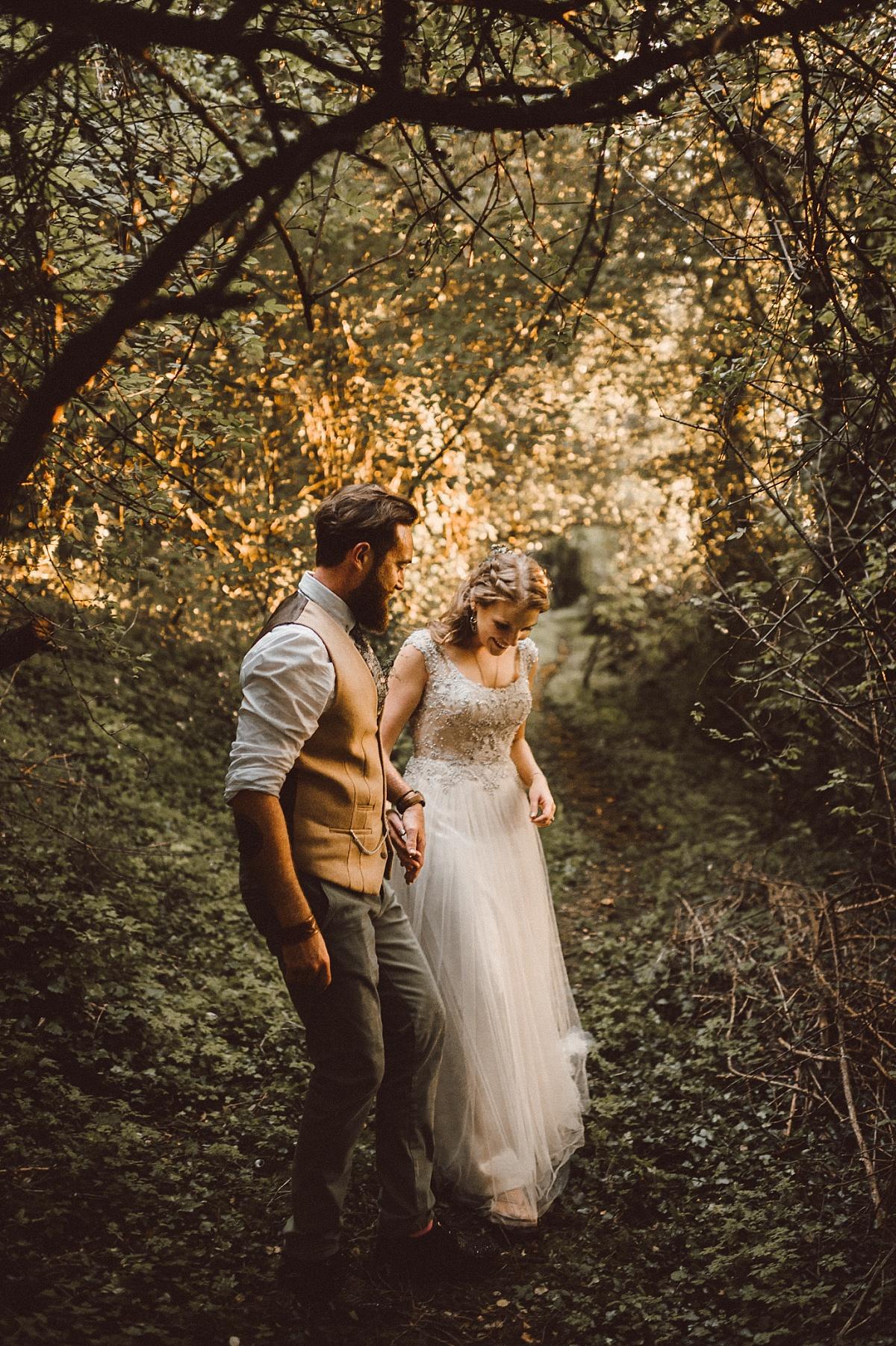 Groom leading bride down path at alternative wedding