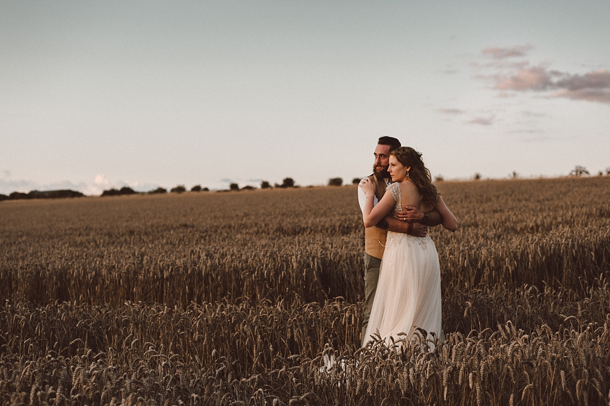 Couple standing in field looking at sunset