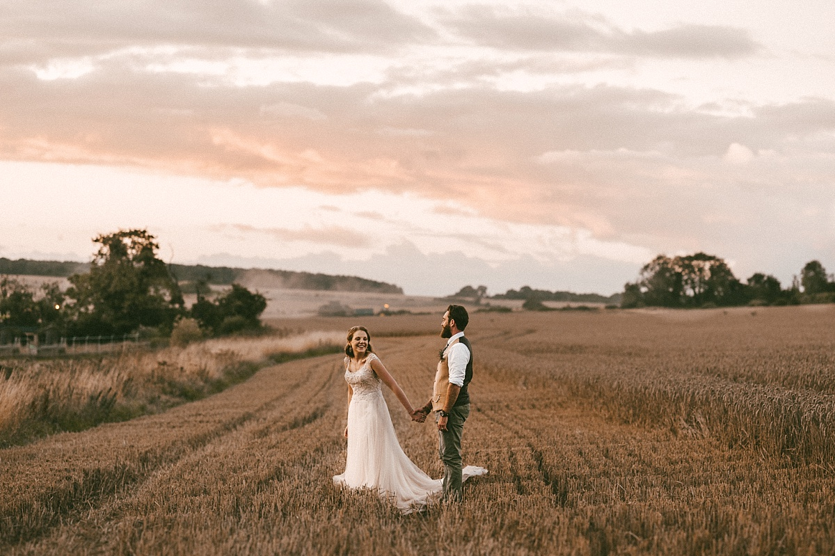Wedding couple standing in field looking at sunet at alternative wedding