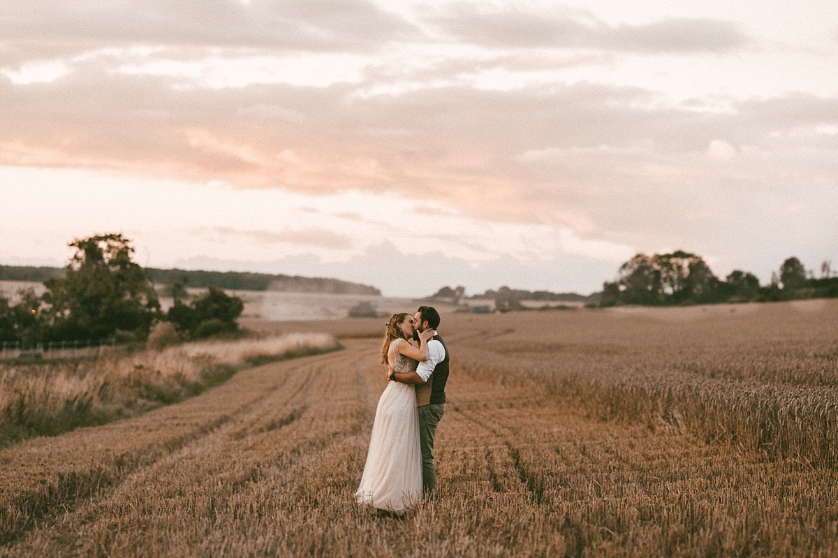 Newly married couple kissing in field