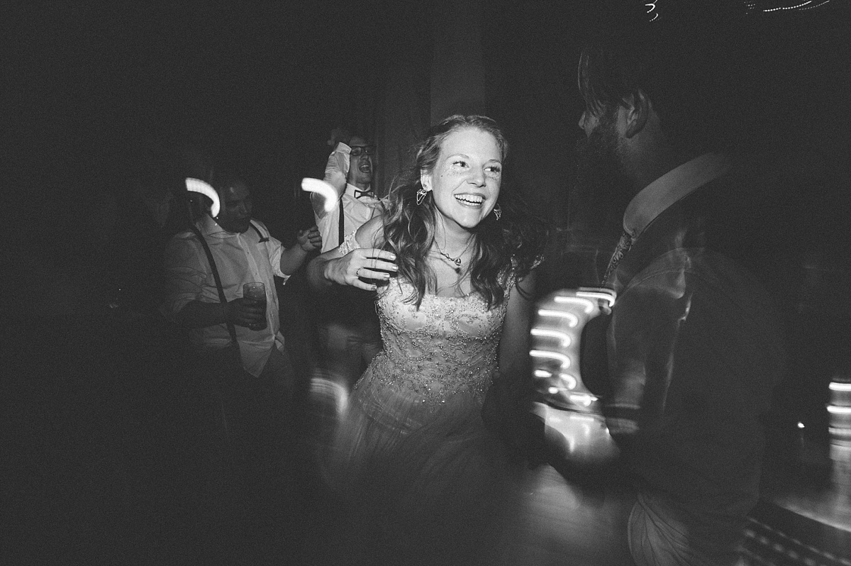 Black & white photo of bride dancing at her wedding