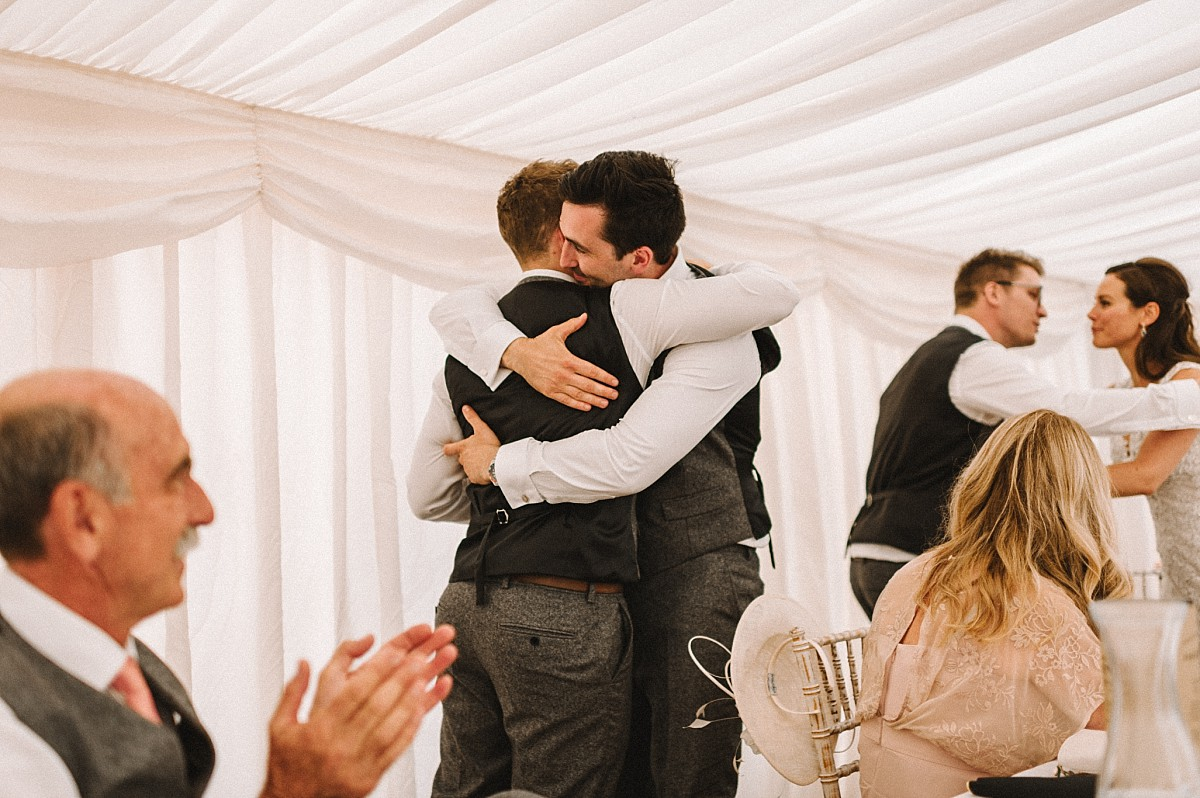 colour photograph of groom hugging bestman