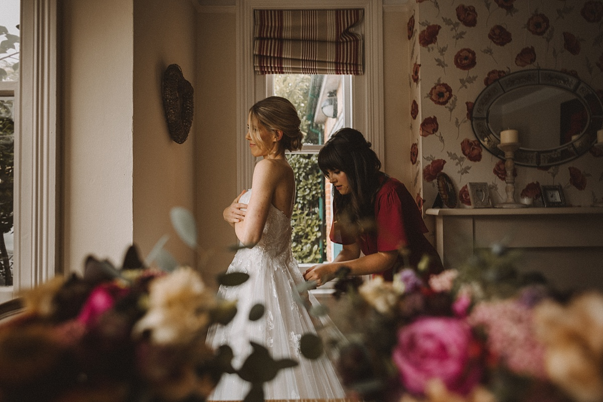 Brides sister helping bride into dress