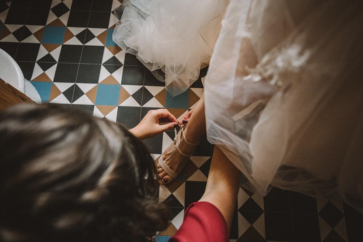Bride doing up wedding shoe