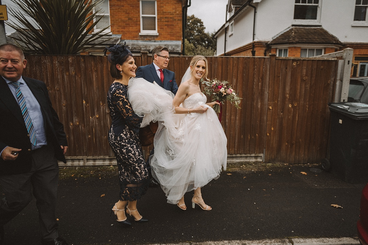 Bride walking to wedding car with family