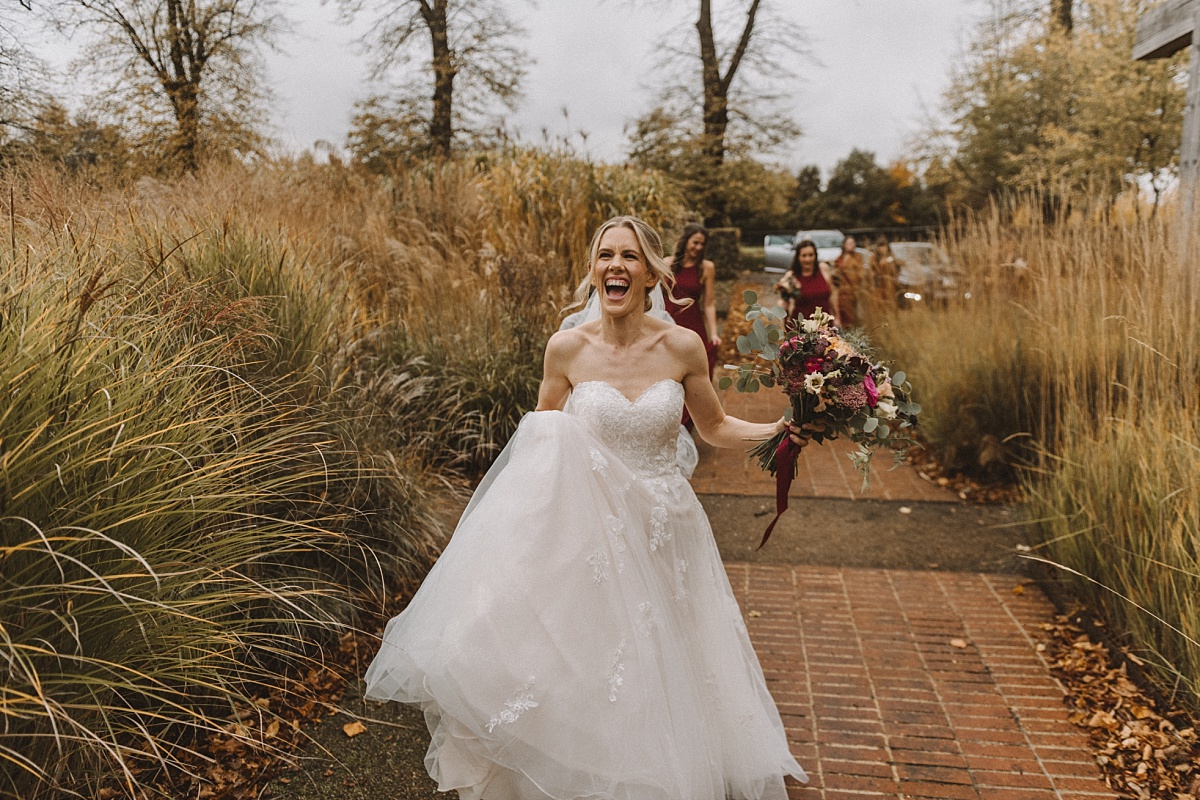 Bride laughing whilewalking into wedding venue in Surrey