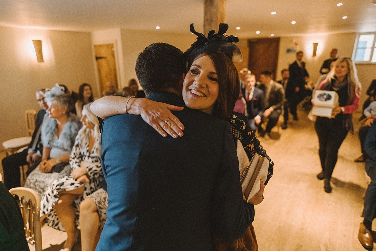 Wedding guest hugging groom to be