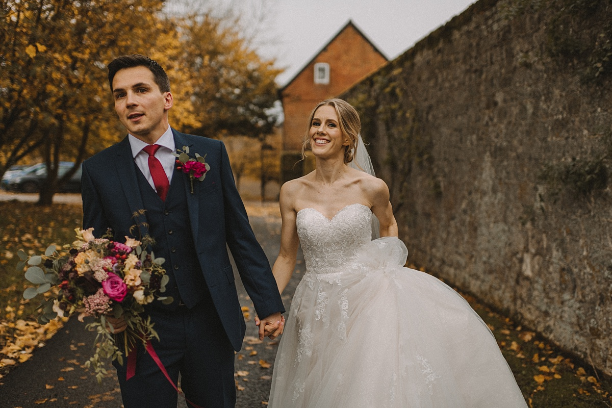 Groom leading along new wife at Bury Court Barn