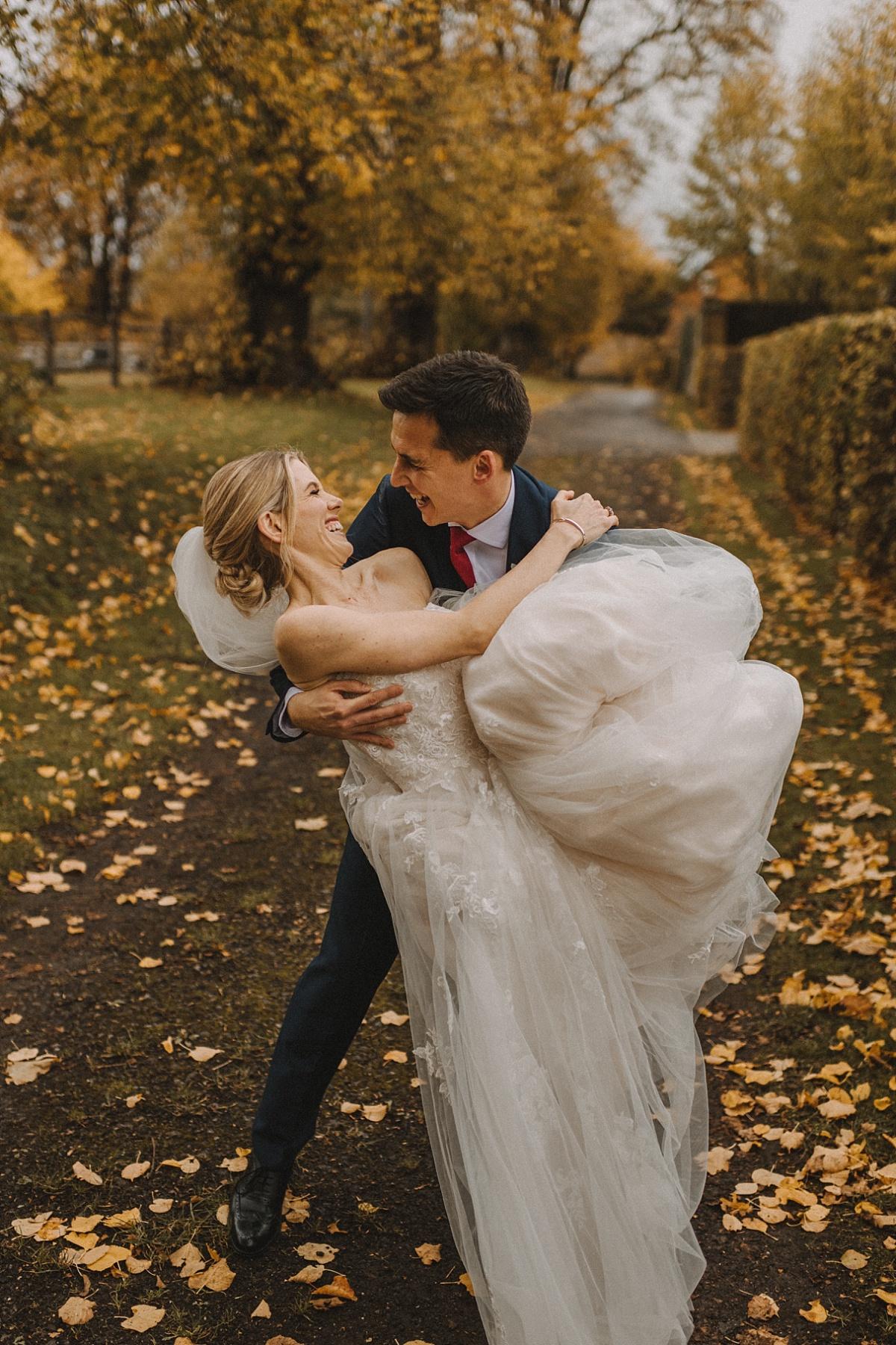 Groom dancing with bride outside of Barn