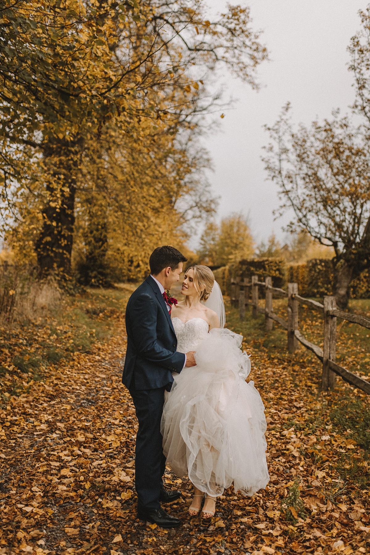 Photo of groom holdingbrides dress at Bury Court Barn