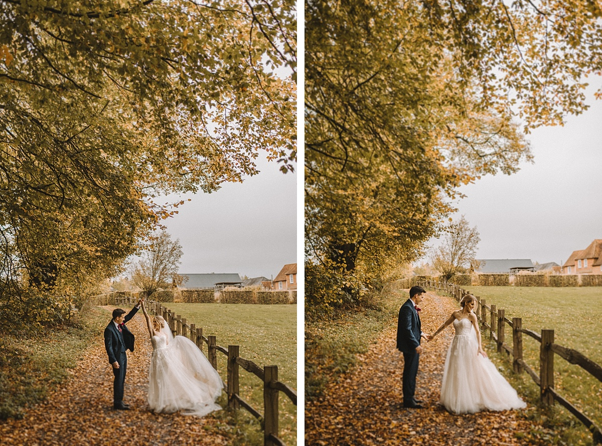 photo of bride& groom dancing on Autumn leaves at Bury Court Barn