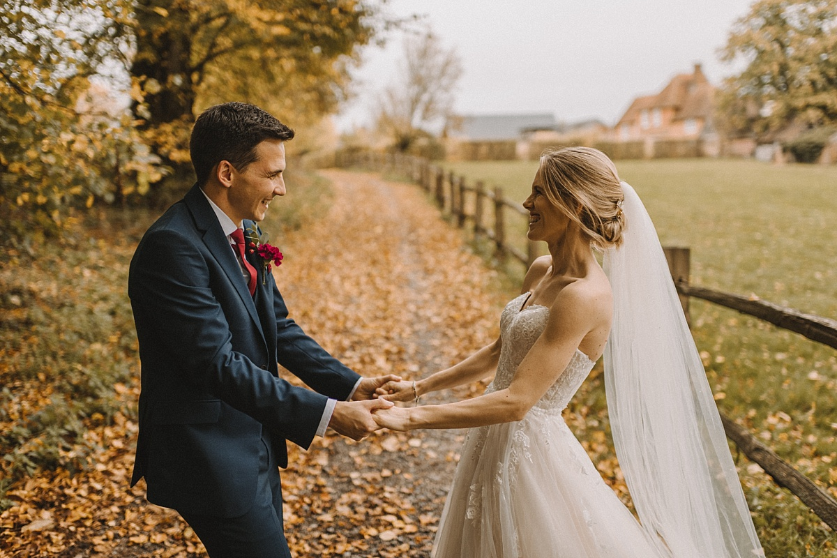 Married couple holding handsand Bury Court Barn in background
