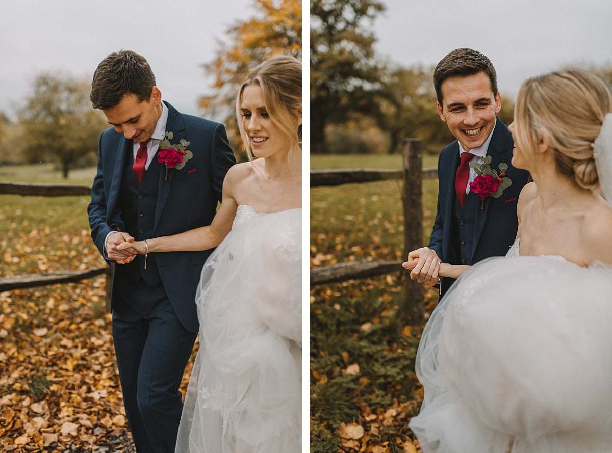 Bride holding Grooms hand with fields behind at Bury Court Barn
