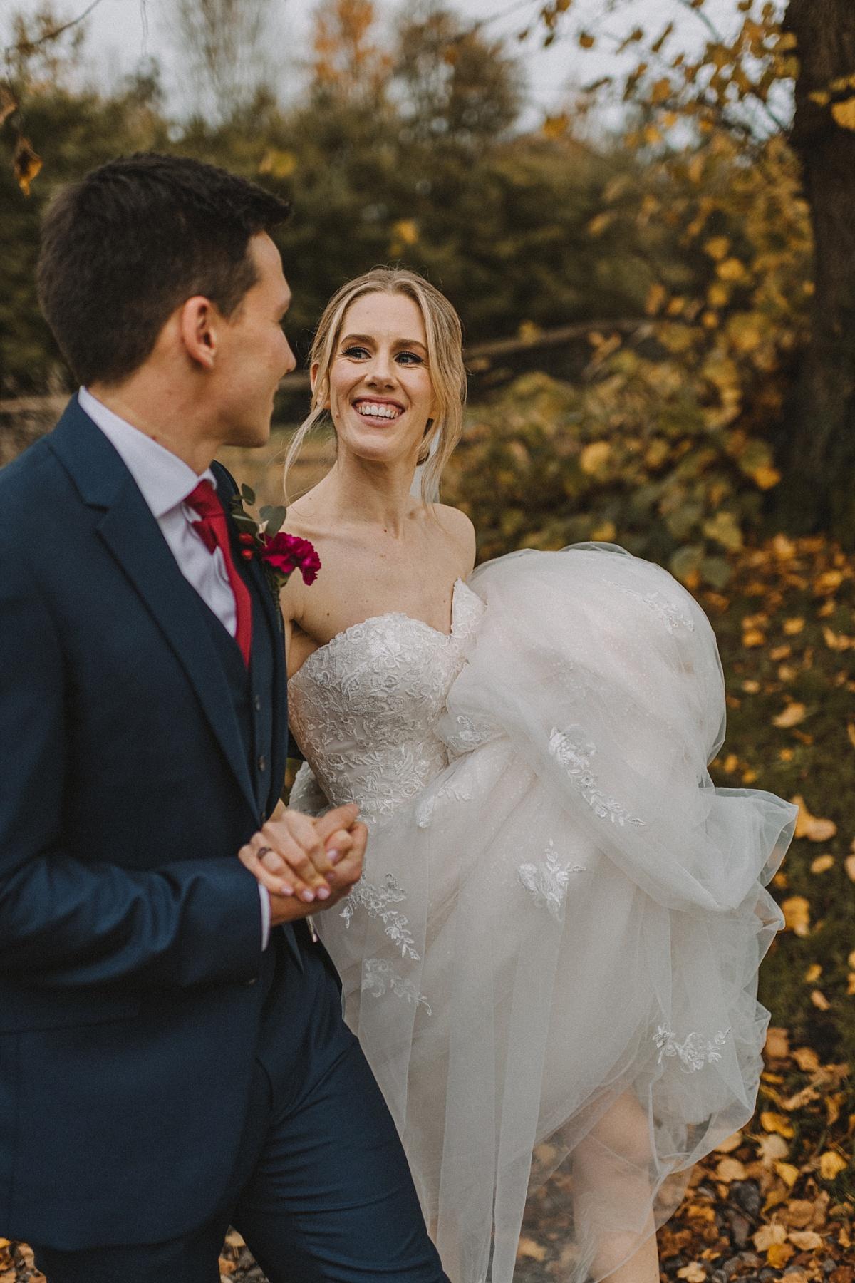 Bride smiling at groom and walking along Bury Court Barn