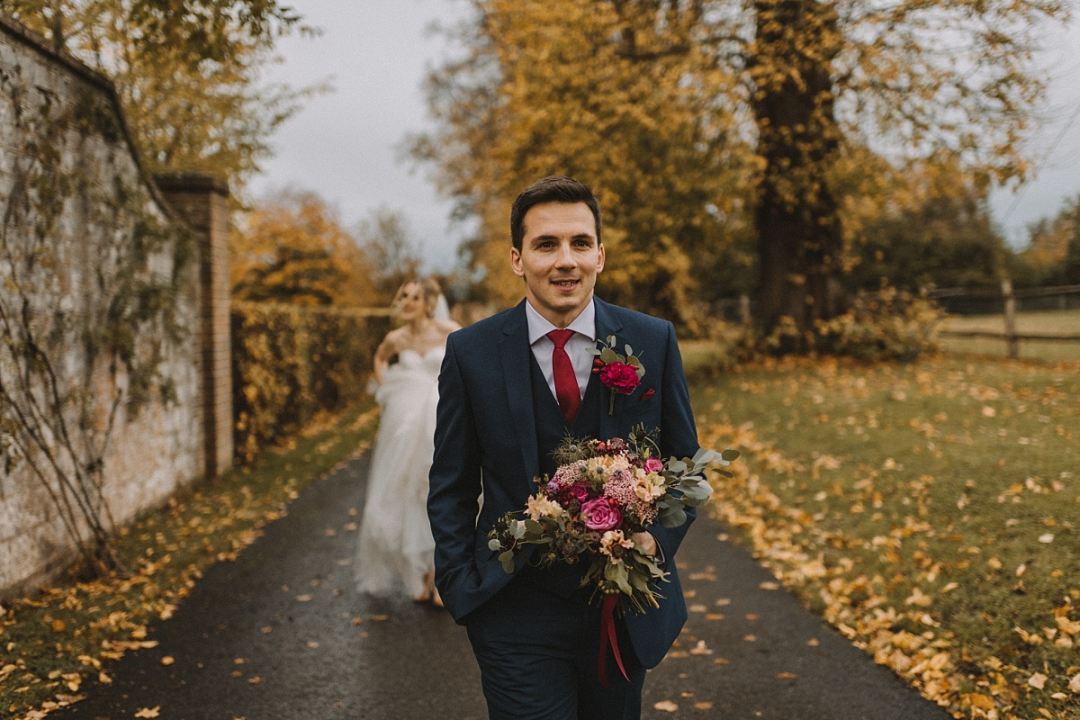 Bride walking along road holding bouquet at Bury Court Barn