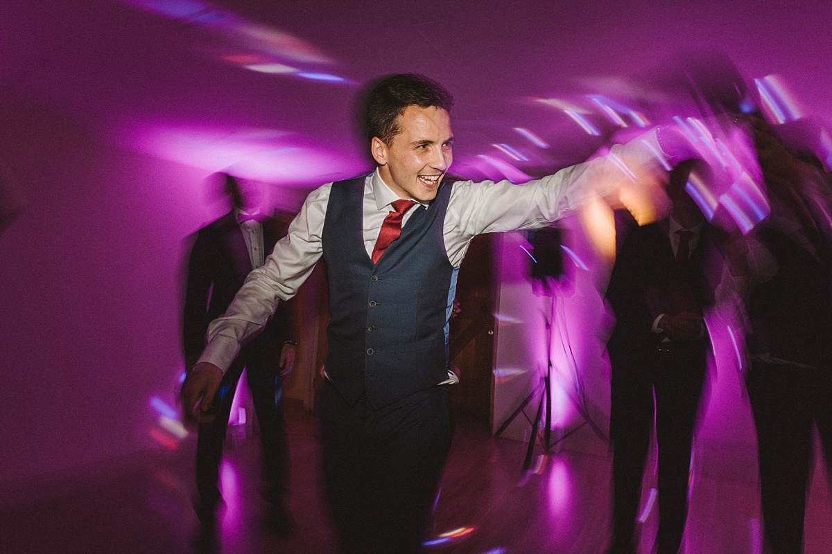 Groom dancing at wedding reception at Bury Court Barn