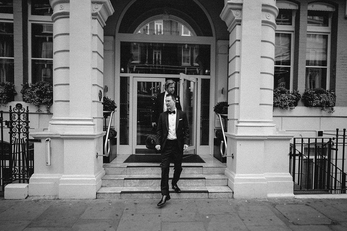 Groom leaving hotel in morning of London wedding