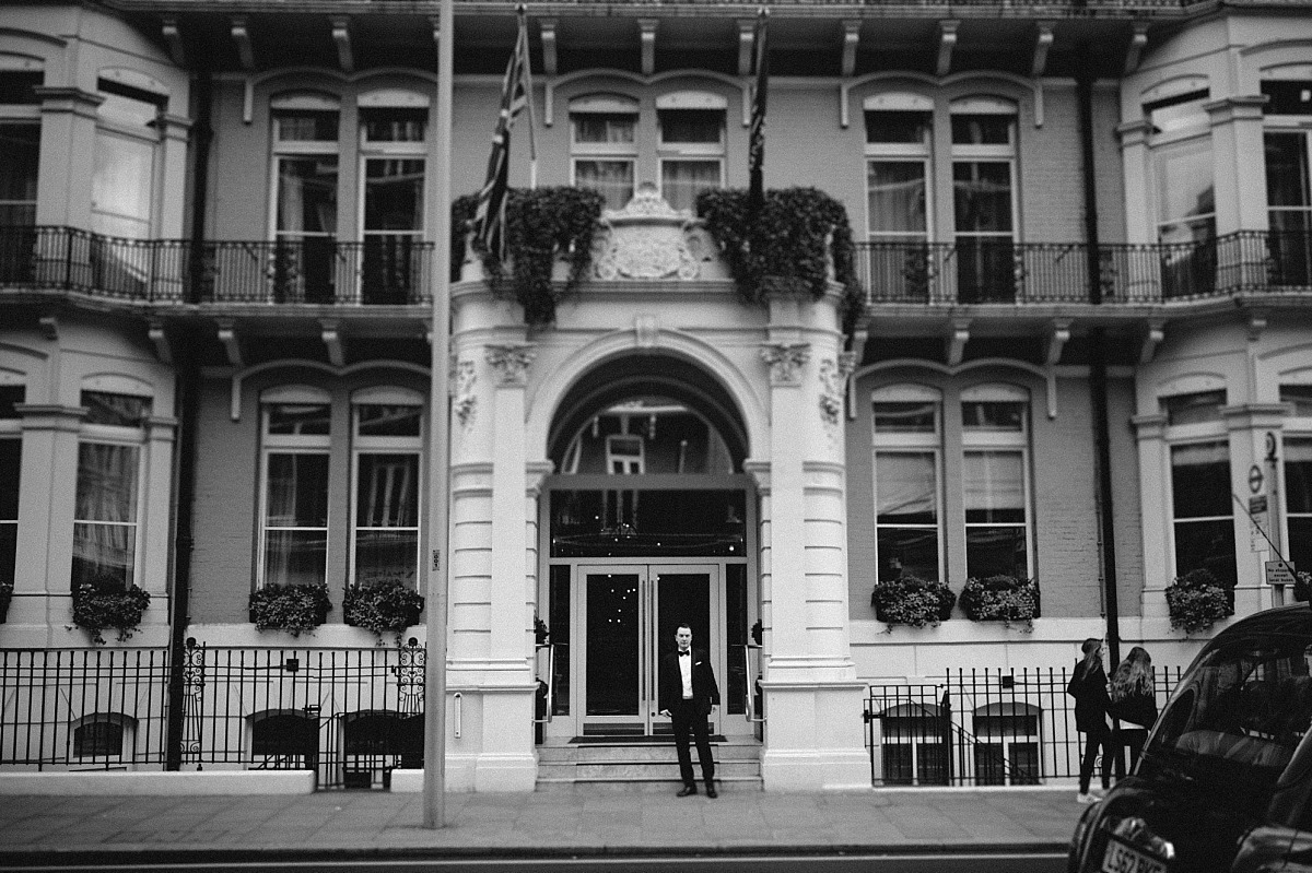 Groom standing outside The Ampersand hotel in London