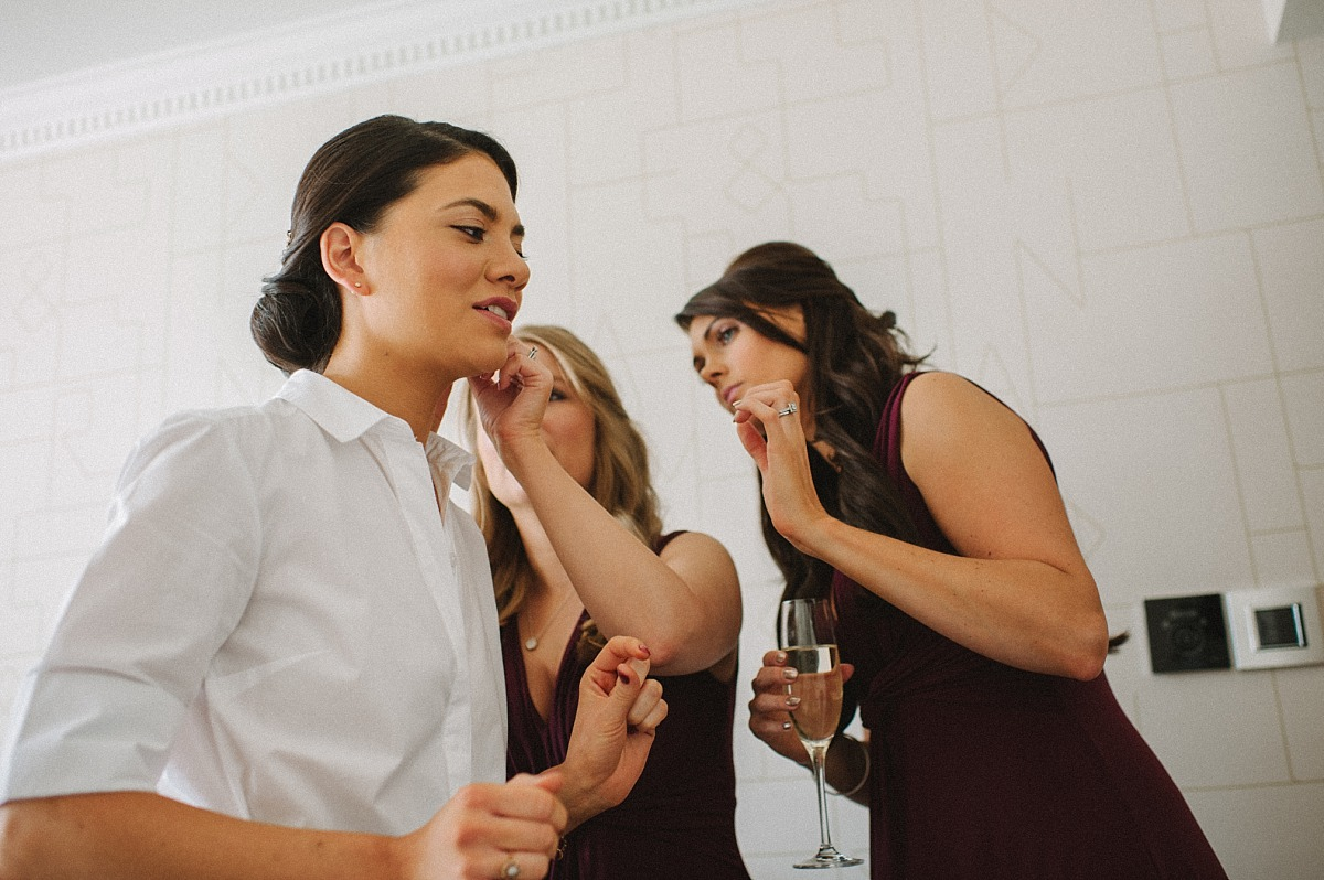 Bridesmaids helping Bride with ear rings