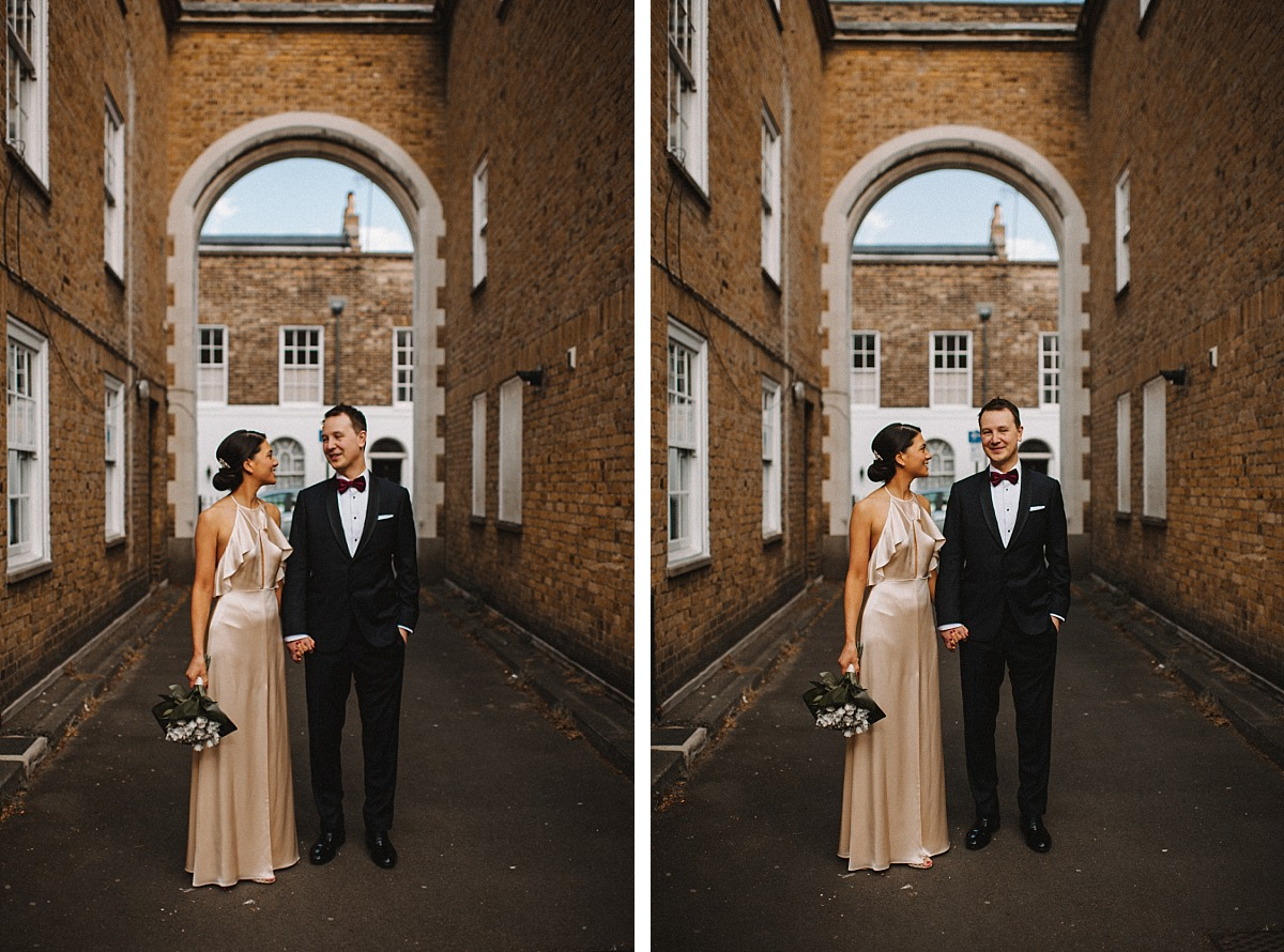 Stylish couple standing under arch in London