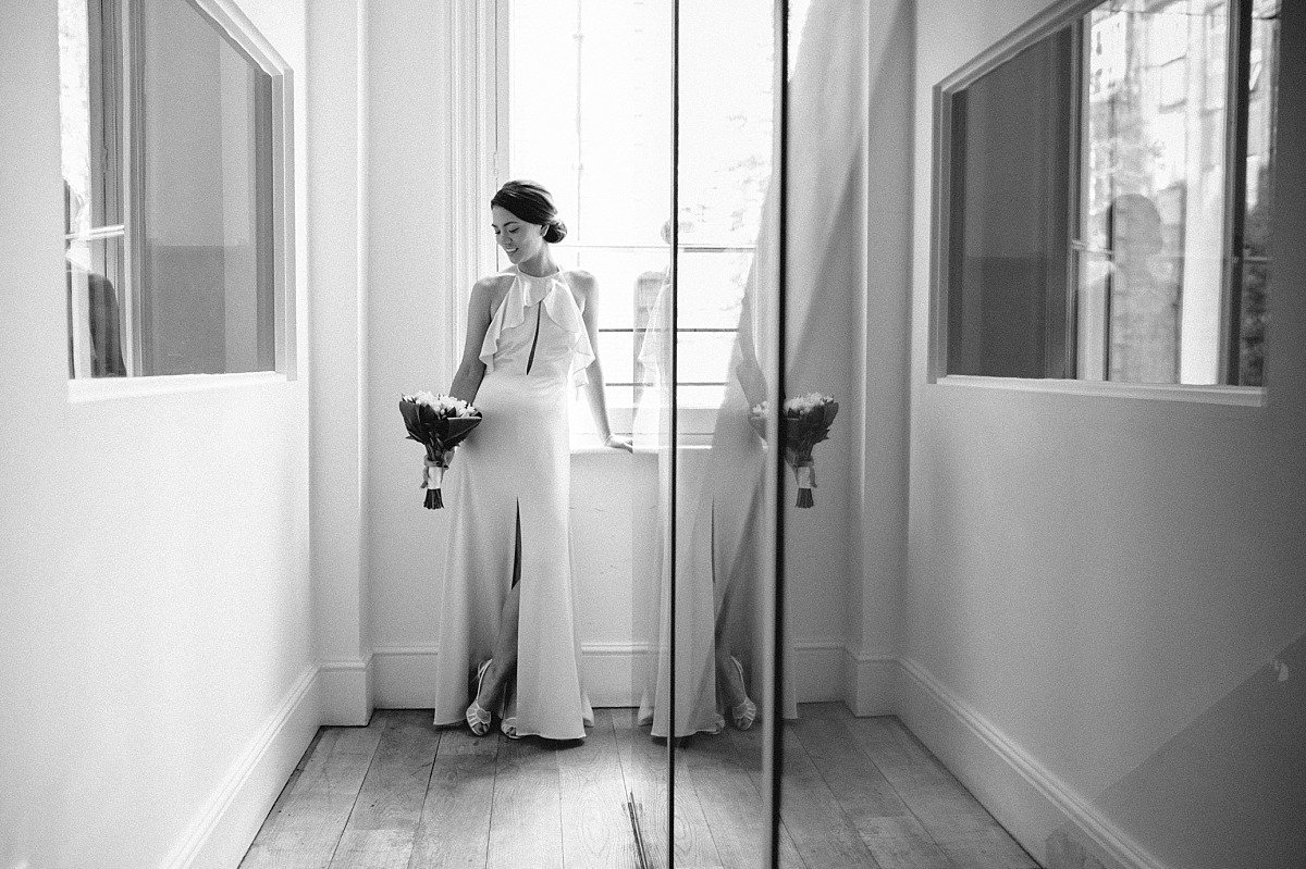 Stylish Bride on wedding day standing in front of window