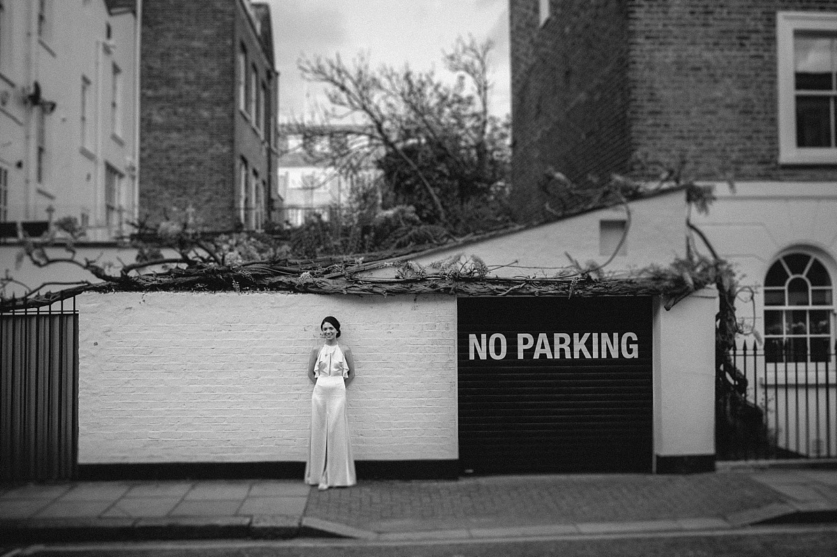 Black & White photograph of stylish Bride infront of garage