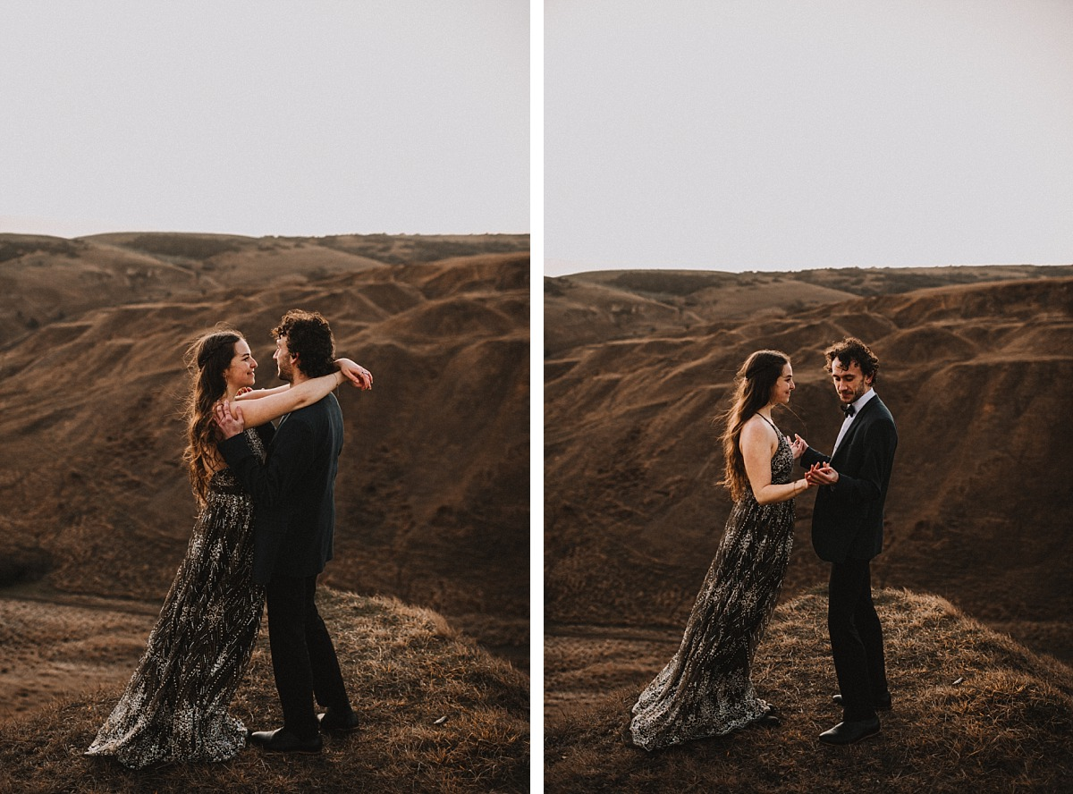 Couple looking at eachother holding hands on top of a hill