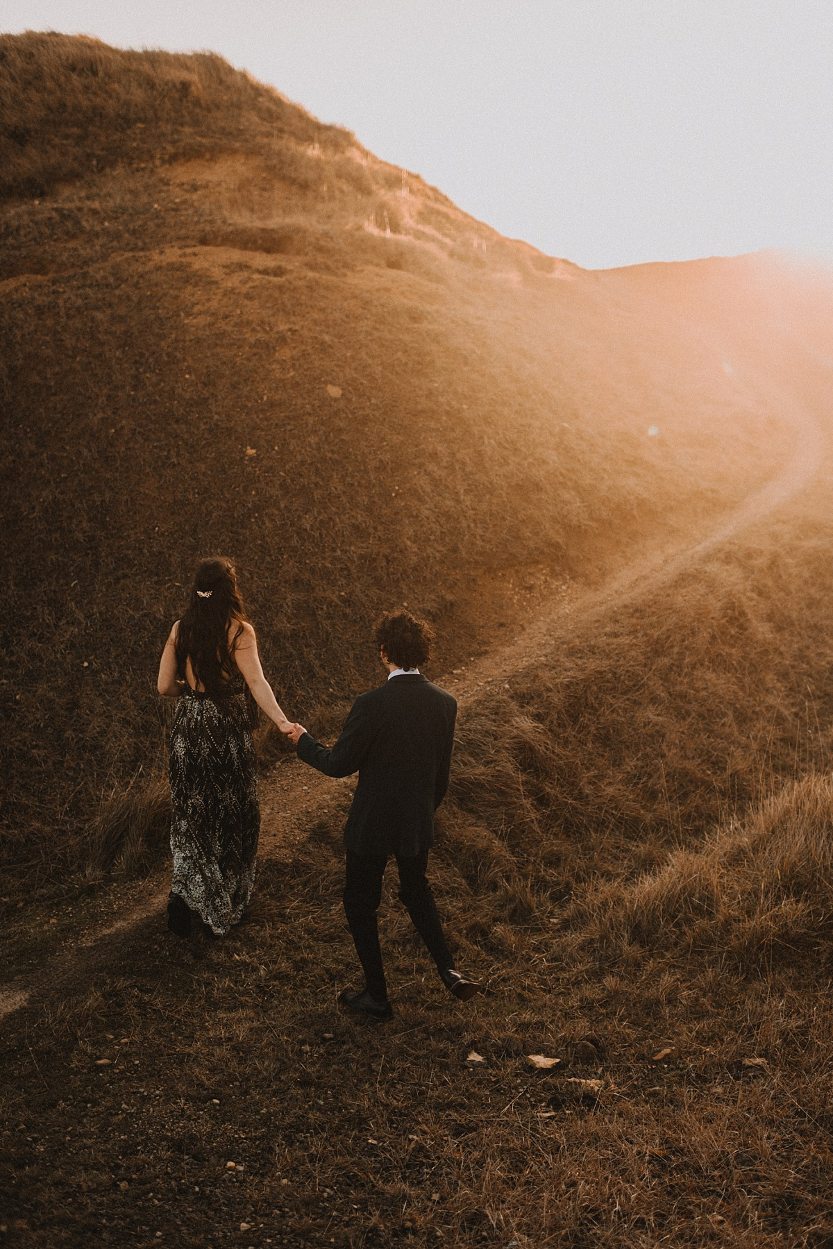 Photo of couple walking into sunrise